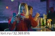 Купить «Young woman sitting by the bartender stand and using her phone - taking a selfie with a drink», видеоролик № 32369816, снято 19 февраля 2020 г. (c) Константин Шишкин / Фотобанк Лори
