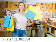 Купить «young woman buys paper packages for gifts», фото № 32382884, снято 19 апреля 2017 г. (c) Яков Филимонов / Фотобанк Лори