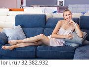 Купить «Woman buyer lying barefoot with pillow on the sofa in furniture shop», фото № 32382932, снято 5 сентября 2017 г. (c) Яков Филимонов / Фотобанк Лори