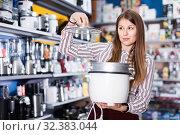 Modern female housewife buying slow cooker in domestic appliances section. Стоковое фото, фотограф Яков Филимонов / Фотобанк Лори