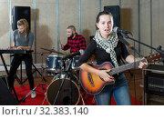 Купить «excited girl rock singer with guitar during rehearsal», фото № 32383140, снято 26 октября 2018 г. (c) Яков Филимонов / Фотобанк Лори