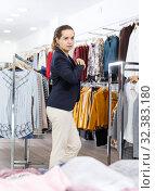 Купить «Woman trying blouse clothing boutique», фото № 32383180, снято 10 октября 2018 г. (c) Яков Филимонов / Фотобанк Лори