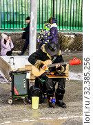 Купить «Уличный  музыкант играет на гитаре, молодые люди фотографируются. Москва, Россия.», фото № 32385256, снято 10 января 2019 г. (c) Владимир Устенко / Фотобанк Лори