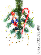 Christmas decorations and tree branch on white background. Striped candy, wooden nutcracker, confetti. Flat lay. New Year and Christmas mood. Стоковое фото, фотограф Papoyan Irina / Фотобанк Лори