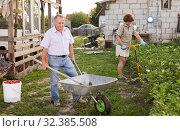 Senior man carrying garden tools in a wheelbarrow. Стоковое фото, фотограф Татьяна Яцевич / Фотобанк Лори