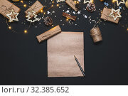 Happy New year 2020. Writing Goals on Kraft paper decorated with Christmas Gold and silver decorations on black background. New year concept. Flat lay, top view, copy space. Стоковое фото, фотограф Сергей Тимофеев / Фотобанк Лори