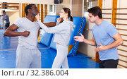 Купить «People fighting with coach at gym», фото № 32386004, снято 31 октября 2018 г. (c) Яков Филимонов / Фотобанк Лори
