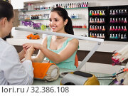 Купить «Manicurists giving manicure to female clients at nail salon», фото № 32386108, снято 28 апреля 2017 г. (c) Яков Филимонов / Фотобанк Лори