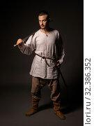 Купить «Young brunet in viking image view in the dark», фото № 32386352, снято 12 октября 2019 г. (c) Гурьянов Андрей / Фотобанк Лори