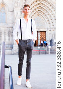 Купить «young European guy in shirt and trousers with suspenders walking around city», фото № 32388416, снято 27 июня 2018 г. (c) Татьяна Яцевич / Фотобанк Лори