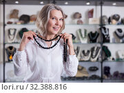 Adult woman trying on a gemstone necklace at a jewelry store. Стоковое фото, фотограф Яков Филимонов / Фотобанк Лори