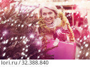 Купить «Woman is preparing for Christmas and choosing X-mas tree», фото № 32388840, снято 21 декабря 2017 г. (c) Яков Филимонов / Фотобанк Лори