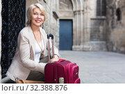 Купить «Mature female tourist is sitting with suitcase», фото № 32388876, снято 3 сентября 2017 г. (c) Яков Филимонов / Фотобанк Лори