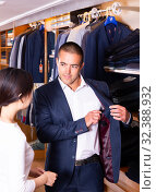 Купить «Smiling couple examining various suits in mens cloths store», фото № 32388932, снято 26 февраля 2020 г. (c) Яков Филимонов / Фотобанк Лори