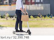 Купить «businessman with takeaway paper bag riding scooter», фото № 32390748, снято 1 августа 2019 г. (c) Syda Productions / Фотобанк Лори