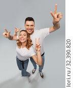 Купить «happy couple in white t-shirts showing peace», фото № 32390820, снято 6 октября 2019 г. (c) Syda Productions / Фотобанк Лори