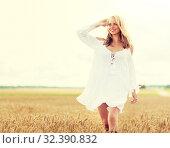 Купить «smiling young woman in white dress on cereal field», фото № 32390832, снято 31 июля 2016 г. (c) Syda Productions / Фотобанк Лори