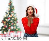 Купить «happy young woman in santa hat sending air kiss», фото № 32390908, снято 30 сентября 2019 г. (c) Syda Productions / Фотобанк Лори