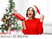 Купить «happy young woman in santa hat with red gift box», фото № 32390916, снято 30 сентября 2019 г. (c) Syda Productions / Фотобанк Лори
