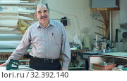 Купить «Portrait of a senior male business owner behind the counter of his workshop, standing and smiling to a camera», видеоролик № 32392140, снято 21 апреля 2017 г. (c) Vasily Alexandrovich Gronskiy / Фотобанк Лори