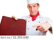 Der Küchenchef empfiehlt mit Zeigefinger die Speisekarte. Стоковое фото, фотограф Zoonar.com/Robert Kneschke / age Fotostock / Фотобанк Лори
