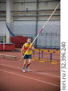Купить «Pole vaulting indoors - a man in yellow shirt about to run up on the track with a pole», фото № 32396240, снято 1 ноября 2019 г. (c) Константин Шишкин / Фотобанк Лори