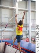 Купить «Pole vaulting indoors - a athletic man jumping over the bar - the pole flexing under the weight», фото № 32396248, снято 1 ноября 2019 г. (c) Константин Шишкин / Фотобанк Лори