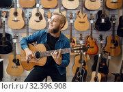 Купить «Young man plays on acoustic guitar in music store», фото № 32396908, снято 11 сентября 2019 г. (c) Tryapitsyn Sergiy / Фотобанк Лори