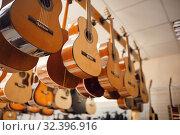 Купить «Rows of acoustic guitars in music store», фото № 32396916, снято 11 сентября 2019 г. (c) Tryapitsyn Sergiy / Фотобанк Лори