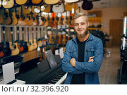 Купить «Young man poses at the showcase in music store», фото № 32396920, снято 11 сентября 2019 г. (c) Tryapitsyn Sergiy / Фотобанк Лори