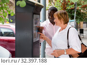 Купить «Polite intelligent African man helping middle aged woman to buy ticket in parking meter on summer city street», фото № 32397188, снято 16 февраля 2020 г. (c) Яков Филимонов / Фотобанк Лори