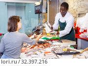 Купить «Salesman serving customer raw fish», фото № 32397216, снято 17 октября 2018 г. (c) Яков Филимонов / Фотобанк Лори
