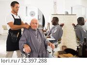Купить «Barber putting on hairdresser cloak to elderly male client», фото № 32397288, снято 22 августа 2019 г. (c) Яков Филимонов / Фотобанк Лори