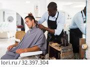 Купить «Man getting haircutting by African barber», фото № 32397304, снято 22 августа 2019 г. (c) Яков Филимонов / Фотобанк Лори