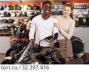 Купить «Smiling man and woman posing on new motorcycle in shop», фото № 32397416, снято 16 января 2019 г. (c) Яков Филимонов / Фотобанк Лори