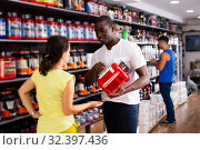Купить «male recommending sports supplements to female», фото № 32397436, снято 18 февраля 2020 г. (c) Яков Филимонов / Фотобанк Лори