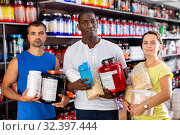 Купить «Smiling young woman and two athletic men holding jars of sports food supplements in shop interior», фото № 32397444, снято 18 февраля 2020 г. (c) Яков Филимонов / Фотобанк Лори