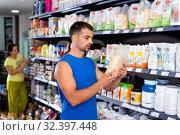 Купить «Focused muscular man looking for necessary sport nutrition products in shop, reading content label», фото № 32397448, снято 8 декабря 2019 г. (c) Яков Филимонов / Фотобанк Лори