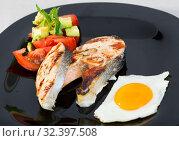 Купить «Grilled salmon with fried egg, tomatoes, avocado on black dish», фото № 32397508, снято 5 декабря 2019 г. (c) Яков Филимонов / Фотобанк Лори