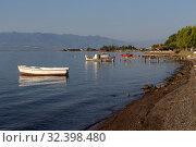 Купить «The fishing boats is moored near the shore and wooden, old pier close-up (Greece)», фото № 32398480, снято 8 сентября 2019 г. (c) Татьяна Ляпи / Фотобанк Лори