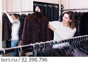 Купить «woman choosing sheepskin coat in women's cloths store», фото № 32398796, снято 23 февраля 2020 г. (c) Яков Филимонов / Фотобанк Лори
