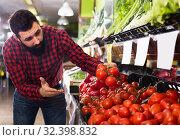 Купить «Laughing male seller offering tomatoes in shop», фото № 32398832, снято 15 ноября 2016 г. (c) Яков Филимонов / Фотобанк Лори