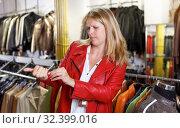 Купить «Woman trying on leather jacket», фото № 32399016, снято 5 сентября 2018 г. (c) Яков Филимонов / Фотобанк Лори