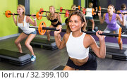 Купить «Portrait of sporty women exercising with barbell in fitness club», фото № 32399100, снято 26 июля 2017 г. (c) Яков Филимонов / Фотобанк Лори