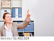 Ältere Frau im Büro hält Zeigefinger hoch auf einen unsichtbaren Touchscreen. Стоковое фото, фотограф Zoonar.com/Robert Kneschke / age Fotostock / Фотобанк Лори