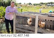 Купить «Farmer man feeding chikens in a hen house», фото № 32407148, снято 12 сентября 2019 г. (c) Яков Филимонов / Фотобанк Лори