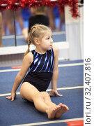 Купить «Young gymnast sitting on gymnastic platform, four years old girl engages in sport school», фото № 32407816, снято 25 декабря 2013 г. (c) Кекяляйнен Андрей / Фотобанк Лори