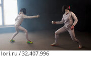 Купить «Two young women having an intense training in a fencing duel in the smoky studio», видеоролик № 32407996, снято 10 апреля 2020 г. (c) Константин Шишкин / Фотобанк Лори
