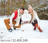 Glückliches Paar posiert mit einem Schneemann im Winter. Стоковое фото, фотограф Zoonar.com/Robert Kneschke / age Fotostock / Фотобанк Лори