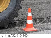 Купить «Wheel with tire on road reclaimer during roadworks, traffic road cone on asphalt», фото № 32410140, снято 27 августа 2019 г. (c) А. А. Пирагис / Фотобанк Лори